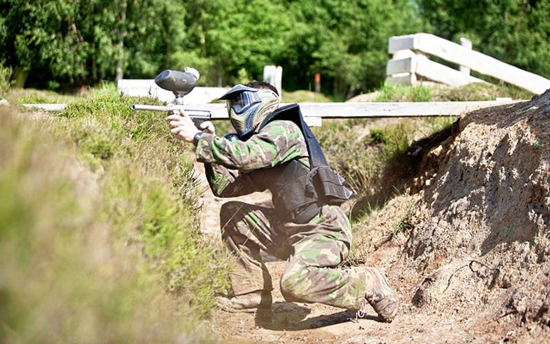 A man crouching down whilst playing paintball
