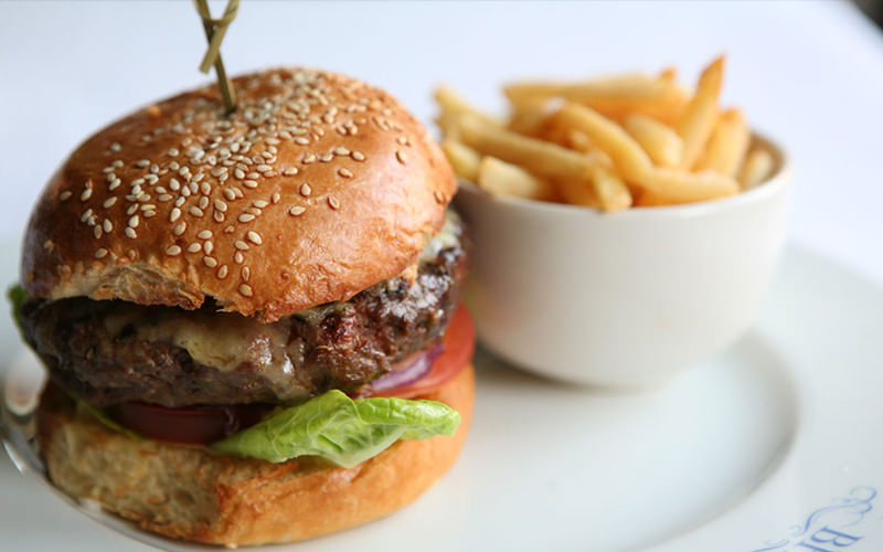Burger and fries on a white plate at Beaufort House, London