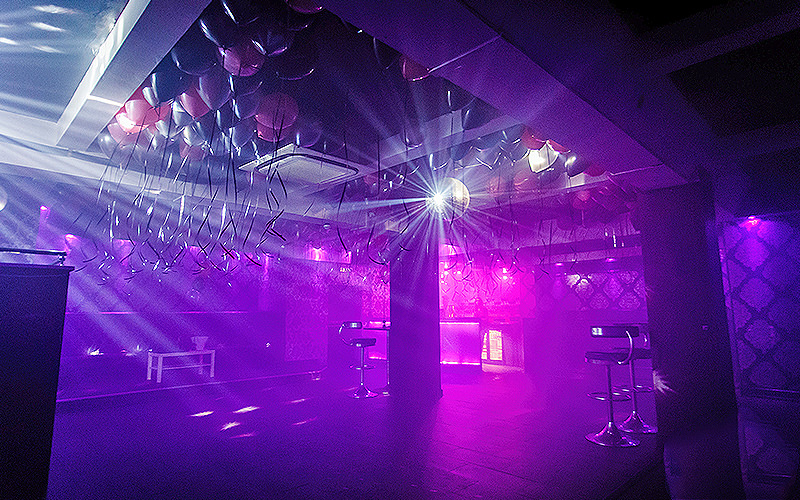 A giant disco ball above a purple, lit up dance floor