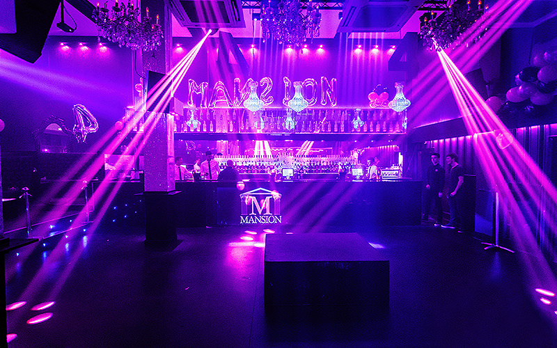 A purple lit up bar, with strobe lights along the dance floor