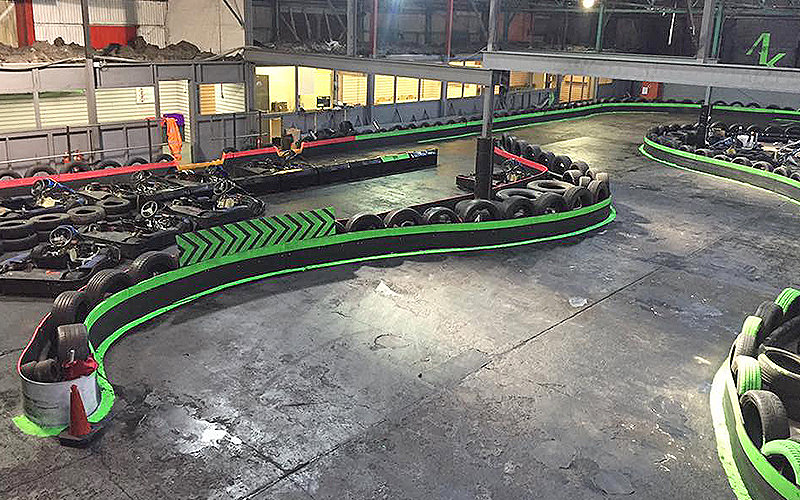 Indoor go karting track, with tyres around the edges of the track