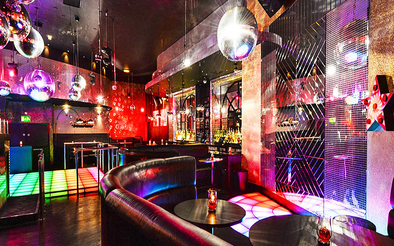 Disco club room, with a groovy dance floor in the background, a black leather booth in the foreground and disco balls hanging from the ceiling