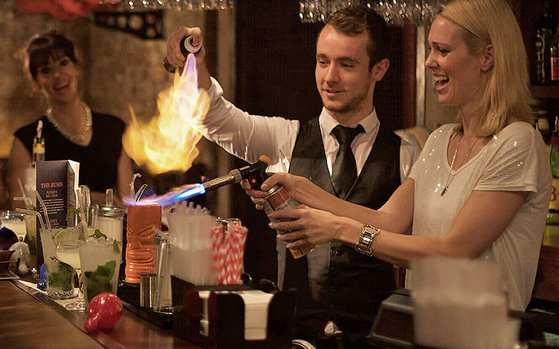 A woman holding a blowtorch over a cocktail as the bartender sprays onto it, with a woman looking on in the background