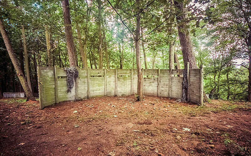 A fence in the middle of an outdoor paintball zone in the forest