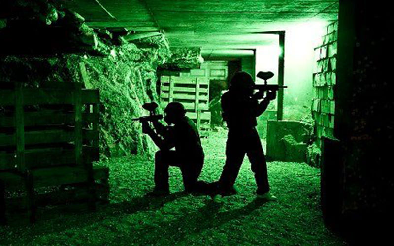 The silhouette of two people in a green lit room and holidng paintball guns