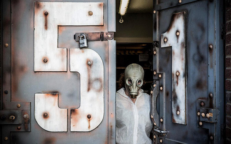 A person in a gas mask and wearing white overalls standing in a steel door marked 51