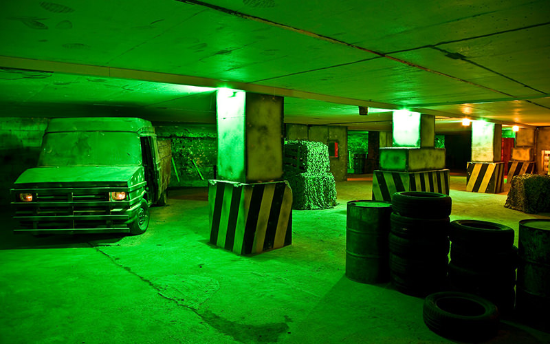 The underground Bunker 51 green lit paintball arena, with a jeep and car tyres placed around the roo