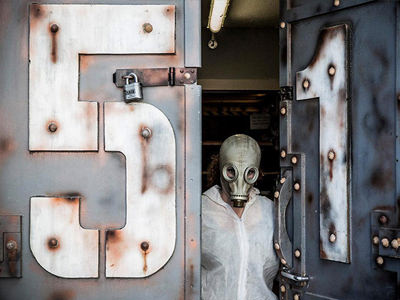A person in a gas mask and white overalls opening a steel door, with the words 51 on it in white