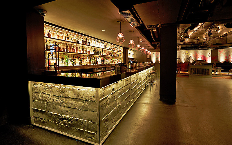 A lit up bar, with a brickwork-look, spirits lined up on the shelves and a column along the side