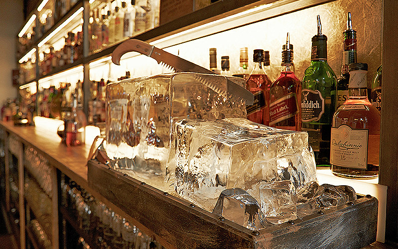 A close up of ice in a metal tray placed on top of a bar, with spirits in the background