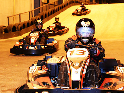 4 go karts racing down the ramp on the track with number 13 leading.