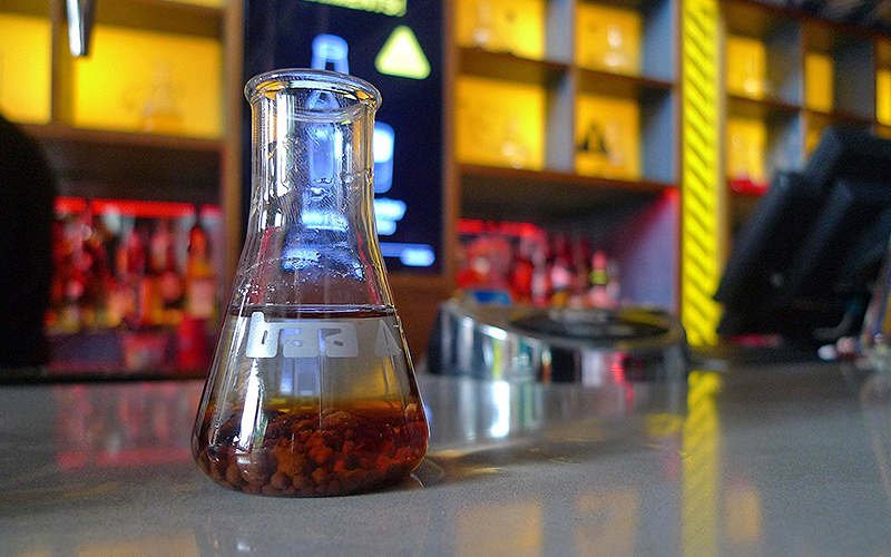 A scientific beaker in the foreground with the background of the bar out of focus