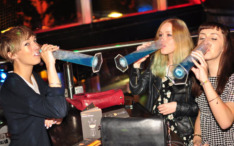 Three girls downing blue drinks out of long containers
