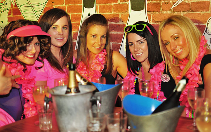Five girls, all wearing floral garlands whilst sitting at a table with champagne buckets in the foreground